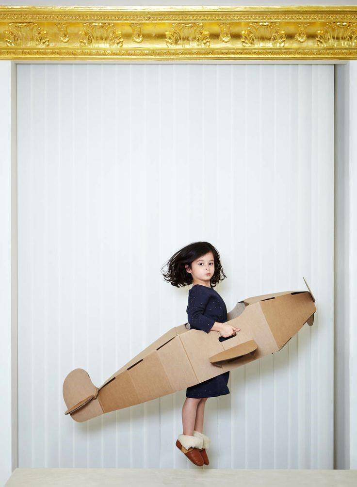 Photo d'une enfant dans un avion en bois
